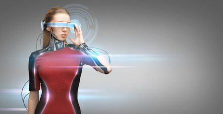 Photo pour people, technology, future and progress - young woman with futuristic glasses and microchip implant or sensors over gray background with virtual projection and laser light - image libre de droit