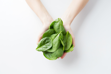 Foto de healthy eating, dieting, vegetarian food and people concept - close up of woman hands holding spinach at home - Imagen libre de derechos