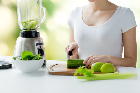 healthy eating, cooking, vegetarian food, dieting and people concept - close up of young woman with blender chopping green vegetables for detox shake or smoothie over natural background