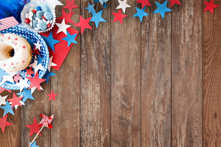 american independence day, celebration, patriotism and holidays concept - close up of glazed donut with candies in disposable tableware and stars at 4th july party from top over wooden background