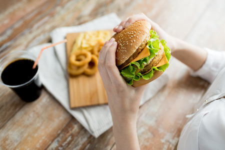 Photo for fast food, people and unhealthy eating concept - close up of woman hands holding hamburger or cheeseburger - Royalty Free Image