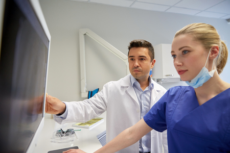 Foto de people, medicine, stomatology, technology and health care concept - dentists looking to x-ray scan on monitor at dental clinic - Imagen libre de derechos