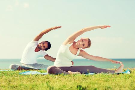 Photo pour fitness, sport, friendship and lifestyle concept - smiling couple making yoga exercises sitting on mats outdoors - image libre de droit