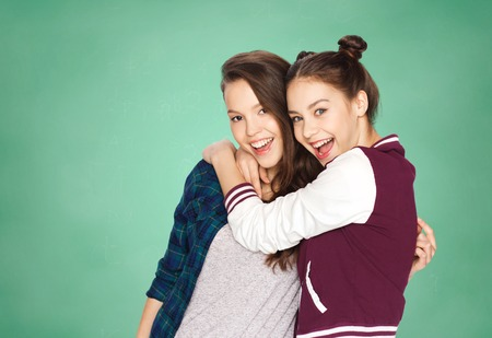 people, friends, teens and education concept - happy smiling pretty teenage girls hugging over green school chalk board background