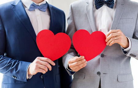 Photo pour people, homosexuality, same-sex marriage, valentines day and love concept - close up of happy married male gay couple holding red paper heart shapes on wedding - image libre de droit