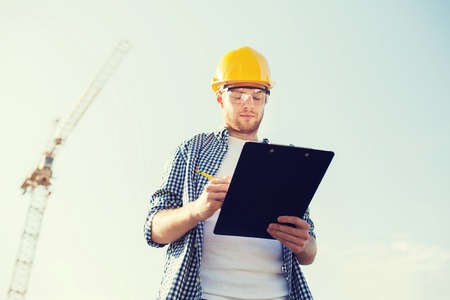 Foto de business, building, paperwork and people concept - builder in hardhat with clipboard outdoors - Imagen libre de derechos