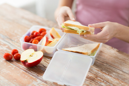 Foto de healthy eating, storage, dieting and people concept - close up of woman with food in plastic container at home kitchen - Imagen libre de derechos