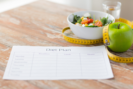 healthy eating, dieting, slimming and weigh loss concept - close up of diet plan paper green apple, measuring tape and salad