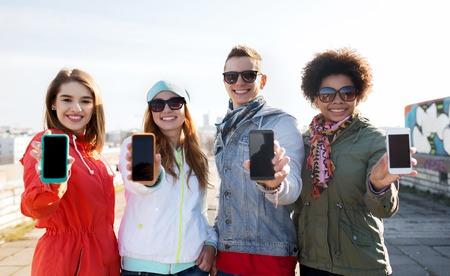 Foto de people, friendship, cloud computing, advertising and technology concept - group of smiling teenage friends showing blank smartphone screens outdoors - Imagen libre de derechos