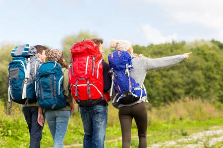 Foto de adventure, travel, tourism, hike and people concept - group of friends walking with backpacks from back - Imagen libre de derechos