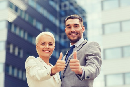 Foto per business, partnership, success, gesture and people concept - smiling businessman and businesswoman showing thumbs up over office building - Immagine Royalty Free