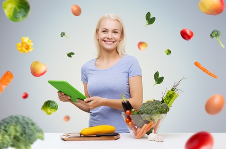 Foto de healthy eating, cooking, vegetarian food, technology and people concept - smiling young woman with tablet pc computer and bowl of vegetables over gray background with falling vegetables - Imagen libre de derechos
