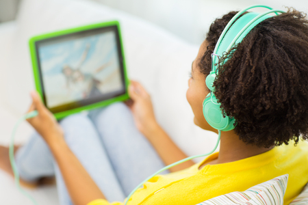 Photo pour people, technology and leisure concept - close up of happy african american young woman lying with tablet pc computer and headphones listening to music and watching video at home - image libre de droit