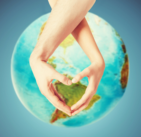 Foto de people, peace, love, life and environmental concept - close up of human hands showing heart shape gesture over earth globe and blue background - Imagen libre de derechos