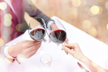 Foto de restaurant, people, celebration and holiday concept - close up of young couple with glasses of red wine at restaurant over holidays lights background - Imagen libre de derechos