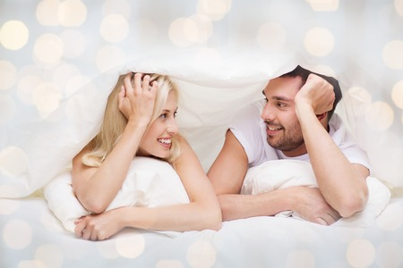 people, family, bedtime and happiness concept - happy couple lying in bed covered with blanket over head and talking at home over lights background
