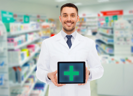 Foto de medicine, pharmacy, people, health care and pharmacology concept - smiling male doctor showing tablet pc computer with cross symbol on screen over drugstore background - Imagen libre de derechos