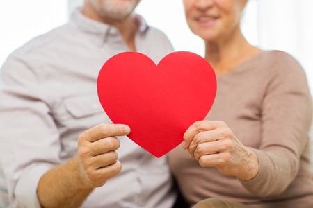 Foto de family, holidays, valentines day, age and people concept - close up of happy senior couple holding big red paper heart shape cutout at home - Imagen libre de derechos