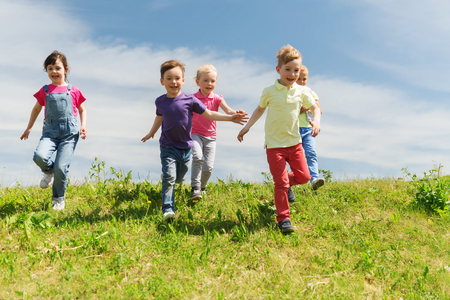 Foto de summer, childhood, leisure and people concept - group of happy kids playing tag game and running on green field outdoors - Imagen libre de derechos
