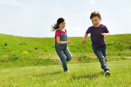 Foto de summer, childhood, leisure and people concept - happy little boy and girl playing tag game and running outdoors on green field - Imagen libre de derechos