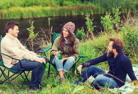 adventure, travel, tourism, friendship and people concept - group of smiling tourists drinking beer in camping
