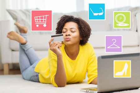 Foto de people, internet bank, online shopping, technology and e-money concept - happy african american young woman lying on floor with laptop computer and credit card at home over internet icons - Imagen libre de derechos