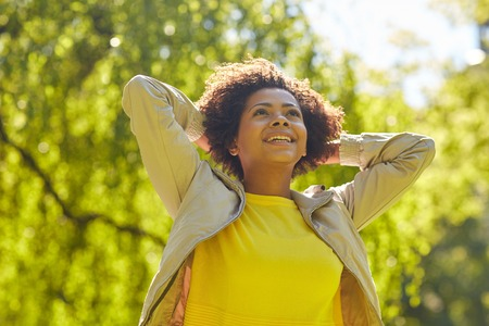 Photo pour people, race, ethnicity and portrait concept - happy african american young woman in summer park - image libre de droit