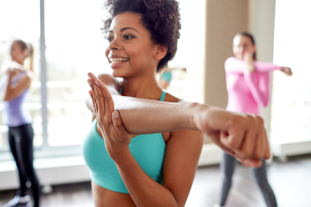 Foto de fitness, sport, dance, people  and lifestyle concept - close up of smiling african american woman with group of women dancing zumba in gym or studio - Imagen libre de derechos