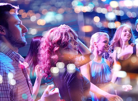 Photo for party, holidays, celebration, nightlife and people concept - smiling friends dancing in club - Royalty Free Image