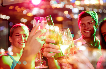 Photo for party, holidays, celebration, nightlife and people concept - smiling friends clinking glasses of champagne and beer in club - Royalty Free Image