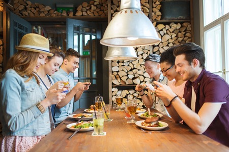 Foto de people, leisure, friendship, technology and internet addiction concept - group of happy smiling friends with smartphones taking picture of food at bar or pub - Imagen libre de derechos