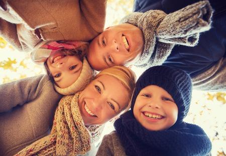 Foto de family, childhood, season and people concept - happy family in autumn park - Imagen libre de derechos