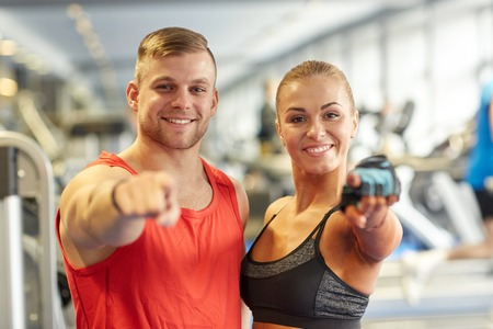 Foto de sport, fitness, lifestyle, gesture and people concept - happy man and woman pointing finger to you in gym - Imagen libre de derechos