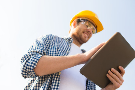 Foto de business, building, industry, technology and people concept - close up of smiling builder in hardhat with tablet pc computer outdoors - Imagen libre de derechos