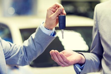 Photo pour close up of male hands with car key in auto show or salon - image libre de droit