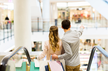 Foto de happy young couple with shopping bags going down by escalator and pointing finger in mall - Imagen libre de derechos