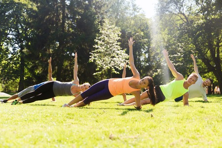 group of happy teenage friends or sportsmen exercising at boot camp