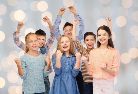 childhood, fashion, gesture and people concept - happy children friends raising fists and celebrating victory over holidays lights background