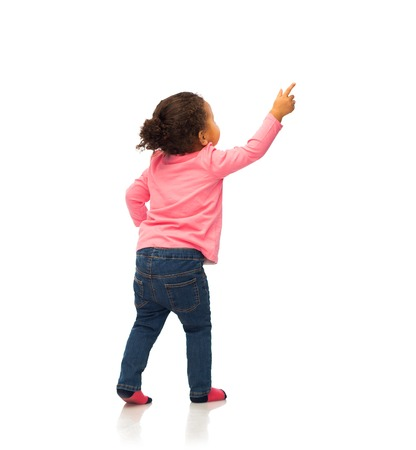 Photo for people, race, ethnicity and childhood concept - happy african american baby girl pointing finger to something from back - Royalty Free Image