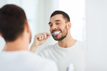 Photo pour health care, dental hygiene, people and beauty concept - smiling young man with toothbrush cleaning teeth and looking to mirror at home bathroom - image libre de droit