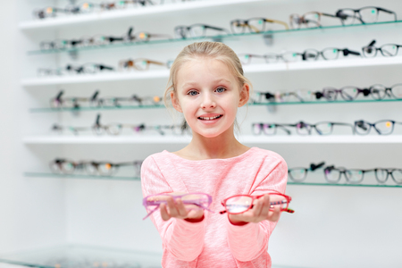 Photo pour health care, people, eyesight and vision concept - little girl in glasses at optics store - image libre de droit