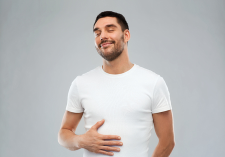 Photo pour satisfaction and people concept - happy full man touching his tummy over gray background - image libre de droit