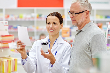 Foto de medicine, pharmaceutics, health care and people concept - happy pharmacist and senior man customer with drug and prescription at drugstore - Imagen libre de derechos