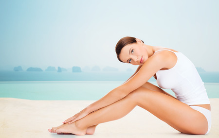 Photo for people, beauty, spa and resort concept - beautiful woman in cotton underwear touching her legs over infinity edge pool background - Royalty Free Image