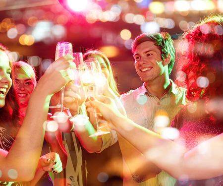 Photo pour party, holidays, celebration, nightlife and people concept - smiling friends clinking glasses of champagne in club - image libre de droit