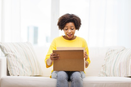 Photo pour people, delivery, shipping and postal service concept - happy african american young woman opening cardboard box or parcel at home - image libre de droit