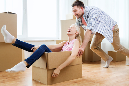 Photo pour home, people, moving and real estate concept - happy couple having fun and riding in cardboard boxes at new home - image libre de droit