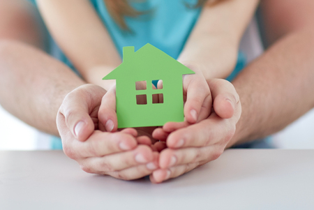 Foto de people, charity, family, real estate and home concept - close up of man and girl holding green paper house cutout in cupped hands - Imagen libre de derechos