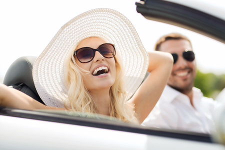 Photo pour transport, leisure, road trip and people concept - happy man and woman driving in cabriolet car outdoors - image libre de droit