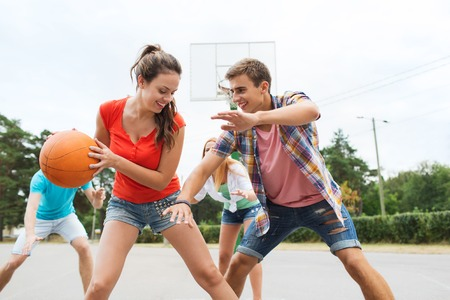 Photo for summer vacation, sport, games and friendship concept - group of happy teenagers playing basketball outdoors - Royalty Free Image